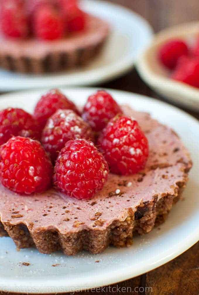 Rich luscious raspberries accompanying a decadent sugar free chocolate tart.