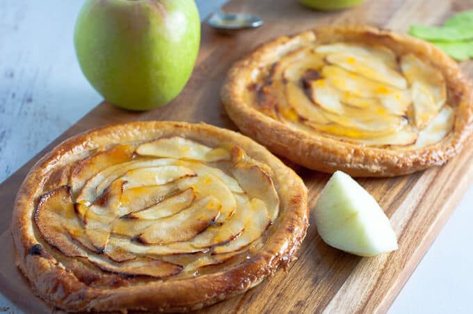 Two apricot tarts on a wooden platter ready to serve
