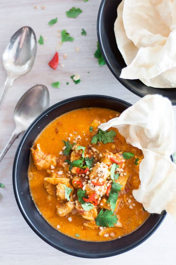 pressure cooker chicken curry in a black bowl with pappduam