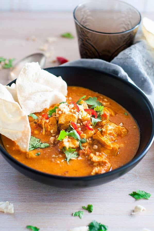 Pressure cooker chicken curry in a black bowl with pappadaum